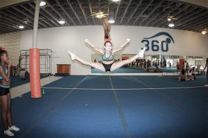 young-female-cheerleader-doing-toe-touch-cheer-stunt-during-practce-toe-touch